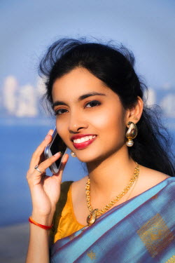 IND7591AW India, Maharashtra, Mumbai, head shot of a young Indian woman in a blue and gold saree smiling and talking on her cell phone MR