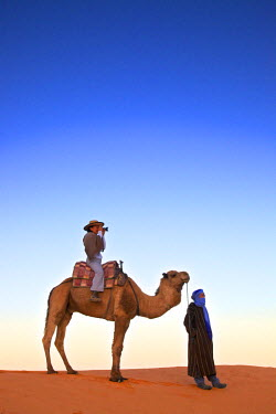 MC02880 Tourist In Desert On Camel Taking A Photograph, Merzouga, Morocco, North Africa (MR)