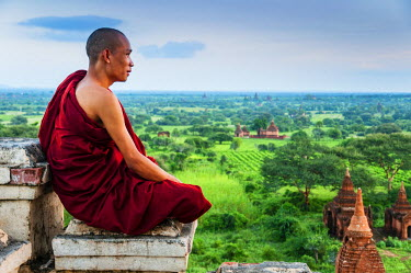 Young buddhist monk sat down on the summit of an old temple in Bagan, Burma or Myanmar