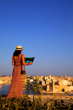 MLT0294 Europe, Maltese Islands, Malta. Young woman looking at a magazine overlooking the three cities from Valletta. MR.
