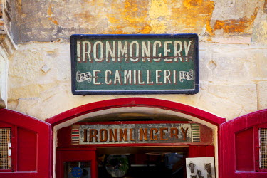 MLT0302 Europe, Maltese Islands, Malta. An ironmonger s shop sign in Valletta dating back to the British rule. UNESCO.