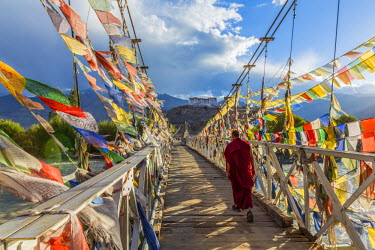 IN03137 Monk & bridge covered in prayer flags, Stakna monastery, nr Leh, Ladakh, India