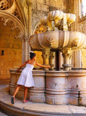 POR7537AW Portugal, Estremadura, Batalha, Monastery of Santa Maria da Vitoria, girl touching fountain (UNESCO World Heritage), (MR)