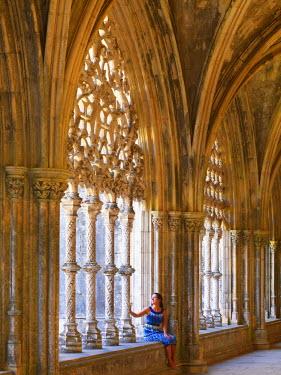 POR7538AW Portugal, Estremadura, Batalha, Monastery of Santa Maria da Vitoria; Woman sitting in cloisters (UNESCO World Heritage) (MR)