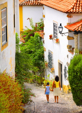 POR7623AW Portugal, Estramadura,Obidos, Woman and girl walking on cobbled street (MR)