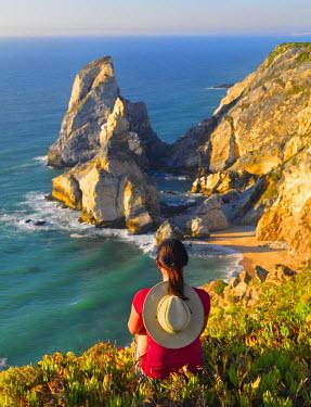 POR7651AW Portugal, Estramadura, Ursa woman sitting on cliff edge (MR)