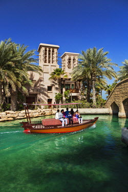 UAE0162 An abra boat ferries tourists around the 5 star Madinat Jumeriah resort complex with the Dar Al Masyaf villas in the background, Umm Suqeim 3, Dubai, The United Arab Emirates.