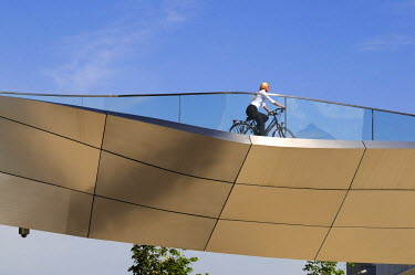 GER8124AW Young woman biking in front of BMW World, Munich, Bavaria, Germany (MR)