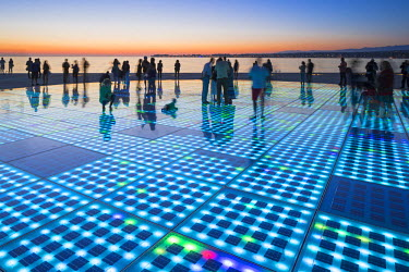 CRO1256AW Croatia, Zadar Region, Zadar. Sunset at the Greeting to the Sun - a 22 metre installation consisting of 300 multi-layered glass plates, designed by Nikola Basic.