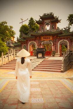 VIT0583AW Woman wearing Ao Dai dress at Phouc Kien Assembly Hall, Hoi An (UNESCO World Heritage Site), Quang Ham, Vietnam (MR)