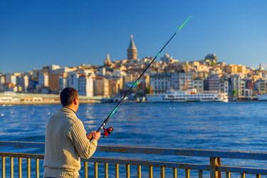 TK01656 Turkey, Istanbul, Beyoglu, Golden Horn, Galata Tower in background, Man Fishing