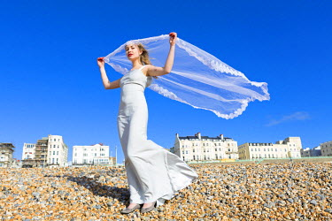 ENG11488AW Europe, United Kingdom, England, East Sussex, Brighton, a bride with a veil blowing in the wind on Brighton beach (MR)