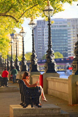 ENG11514AW Europe, United Kingdom, England, London, Westminster, young woman smoking a cigarette while sitting on a bench on the south bank of the Thames
