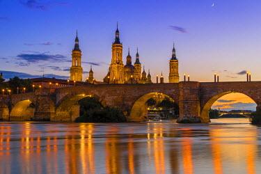 SPA5512AW Sunset view of Puente de Piedra bridge with Basilica de Nuestra Senora del Pilar church, Zaragoza, Aragon, Spain