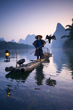 CH10212AW China, Guanxi, Yangshuo. Old chinese fisherman at sunrise on the Li river, fishing with cormorants (MR)