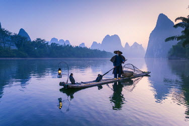 CH10213AW China, Guanxi, Yangshuo. Old chinese fisherman at sunrise on the Li river, fishing with cormorants (MR)