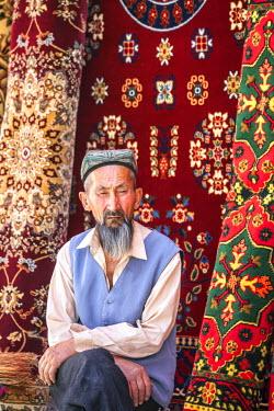 CH10244AW China, Xinjiang, Kashgar. Uyghur man selling carpets at the bazaar