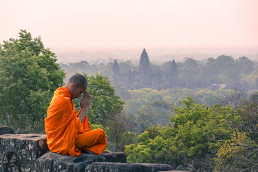 CMB1399AW Cambodia, Siem Reap, Angkor Wat complex. Monk meditating with Angor wat temple in the background (MR)