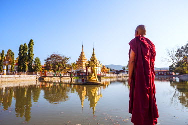 MYA1833AW Myanmar, Hsipaw. Buddhist monk looking at pagodas reflected into small lake (MR)
