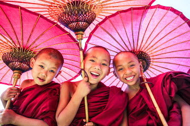 MYA1838AW Myanmar, Mandalay division, Bagan. Portrait of three novice monks under red umbrellas (MR)