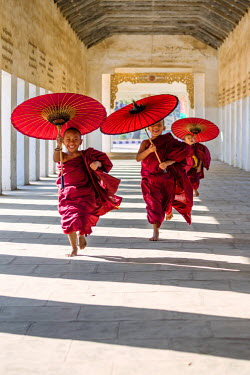 MYA1842AW Myanmar, Mandalay division, Bagan. Three novice monks running with red umbrellas in a walkway (MR)