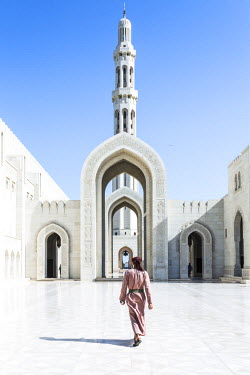 OMA2470AW Oman, Muscat. Omani guard walking to the entrance of Sultan Qaboos Grand Mosque
