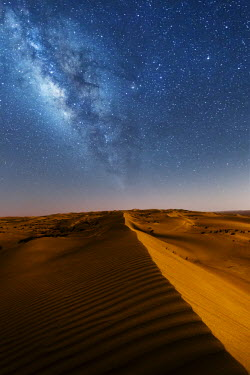 OMA2505AW Oman, Wahiba Sands. The sand dunes at night lit by the moon with the milky way