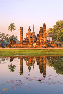 Thailand, Sukhothai Historical Park. Buddhist monks praying at Wat Mahathat temple at sunrise (MR)