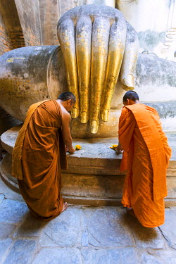 Thailand, Sukhothai Historical Park. Buddhist monks presenting offers at Wat Si Chum temple (MR)
