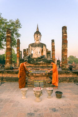 THA0751AW Thailand, Sukhothai Historical Park. Two buddhist monks offering flowers at Wat Mahathat temple at sunrise (MR)