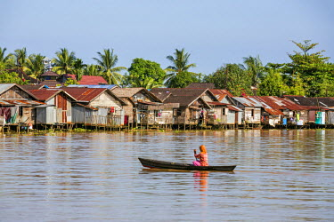 IDA0408 Indonesia, South Kalimatan, Banjarmasin. A woman rows towards houses on stilts lining the banks of the Barito River.  Approximately 25% of Banjarmasin�s population of 800,000 people live along its riv...