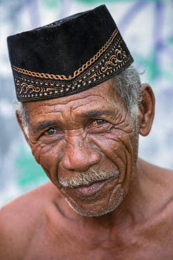 IDA0561 Indonesia, Flores Island, Wuring. An old man at Wuring fishing village wearing a traditional Indonesian black velvet cap known as a peci.