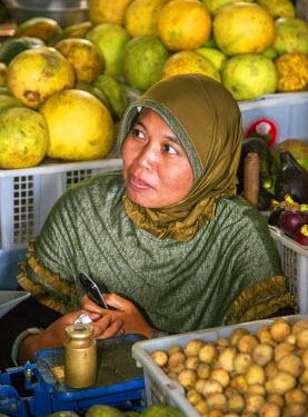 IDA0583 Indonesia, Java, Karangpandan. A woman selling fruit and vegetables at Karangpandan market.  Most Indonesians own mobile phones.