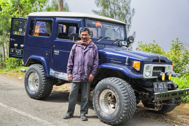 IDA0656 Indonesia, Java, Tosari. The proud owner of a short wheelbase Land Cruiser with large tyres. These 1980s cross-country vehicles are beautifully maintained and are extensively used to take tourists to...