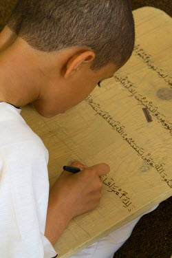 AF55CCE0486 Zliten, Libya. Boy Writes Verses from the Koran on his Prayer Board. He studies to memorize the Koran, working under the supervision of a teacher, or muqri.