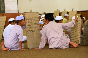 AF55CCE0487 Zliten, Libya. Boys Wait for their Teacher, or Muqri, to Examine their Verses from the Koran Written on their Prayer Boards. Their course of study eventually leads to the memorization of the Koran.