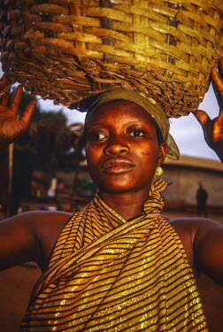 AF19AJN0095 Ghana, Kabile, Brong-Ahafo Region. Portrait of Ghanaian woman wearing gold fabric dress and carrying basket on her head.