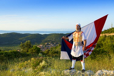 CRO1319AW Europe, Croatia, Dalmatia, Korcula Island, Blato, a local in traditional dress bearing a Croatian flag with Blato town behind