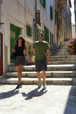 CRO1323AW Europe, Croatia, Dalmatia, Korcula island, Korcula town, a couple walking through the streets of the old town, MR