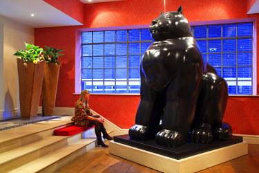 HMS0177162 United Kingdom, London, Soho District, The Soho Hotel, young woman in the lobby in front of a cat sculpture by Fernando Botero