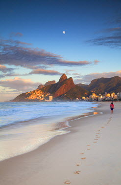 BRA2370AW Woman walking on Ipanema beach at dawn, Rio de Janeiro, Brazil