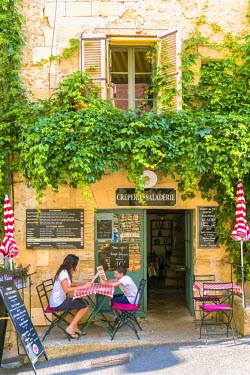FRA8360AW France, Provence Alps Cote d'Azur, Vaucluse, Gordes. Two tourists eating outdoors at a local creperie (MR)