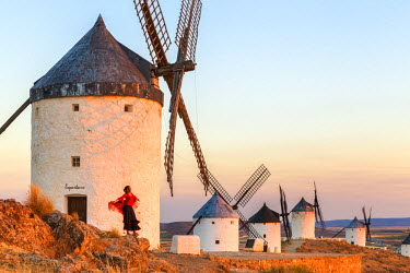 SPA5847AW Spain, Castile-La Mancha, Consuegra. Windmills at sunrise, with woman in spanish traditional clothing (MR)