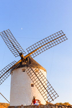 SPA5854AW Spain, Castile-La Mancha, Consuegra. Woman looking at the famous windmills on the Don Quixote route, at sunset (MR)