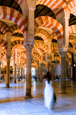 SPA5870AW Spain, Andalusia, Cordoba. Interior of the Mezquita (Mosque) of Cordoba, famous arcaded hypostyle hall, woman with long dress walking (MR)