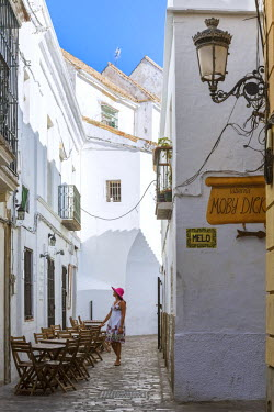 SPA5949AW Spain, Andalusia, Cadiz province, Tarifa. Woman walking in a street of the old town (MR)