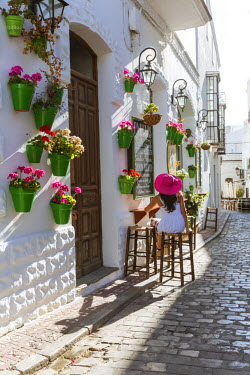 SPA5953AW Spain, Andalusia, Cadiz province, Tarifa. Woman sitting at a caf� in the streets of the old town surrounded by flowers (MR)