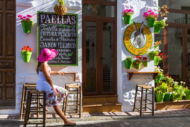 SPA5956AW Spain, Andalusia, Cadiz province, Tarifa. Woman sitting at a caf� in the streets of the old town surrounded by flowers (MR)