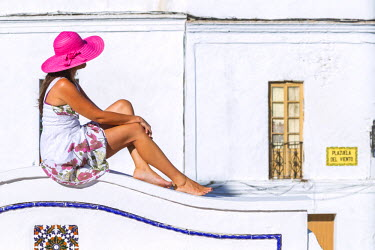 SPA5957AW Spain, Andalusia, Cadiz province, Tarifa. Woman sitting on a white wall in the old town (MR)