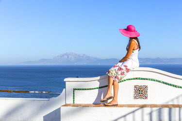SPA5959AW Spain, Andalusia, Cadiz province, Tarifa. Tourist looking at the Straits of Gibraltar from a wall in the old town, the moroccan coast visible in the background (MR)
